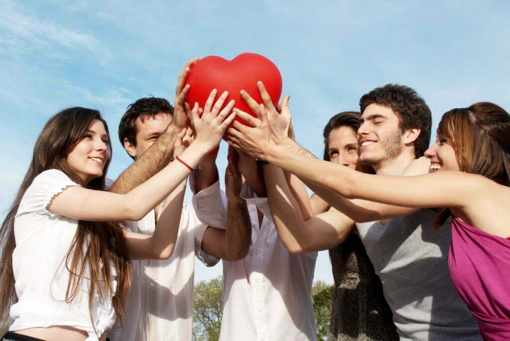 Group of young guys and girls with a sphere in the form of heart
